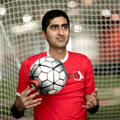 Haseeb Goheer, standing in front of a goal net and holding a soccer ball.